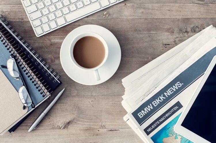 Arbeitsplatz mit Tasse Kaffee, Zeitung, Tastatur und Schreibunterlagen.