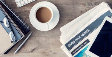 Arbeitsplatz mit Kaffee, Zeitungen, Tastatur und Brille.