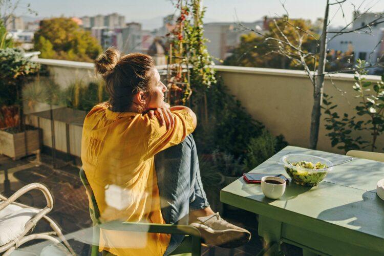Eine Frau sitzt mit Salat und Getränk in der Sonne.