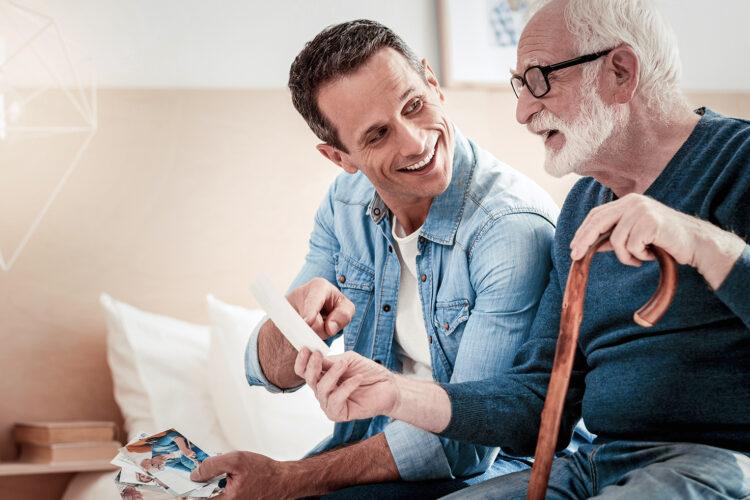 Glücklicher Mann und sein Vater betrachten gemeinsam ein Foto.