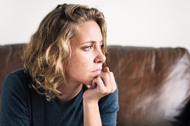 Frau mit ernstem Gesichtsausdruck auf einer Couch.